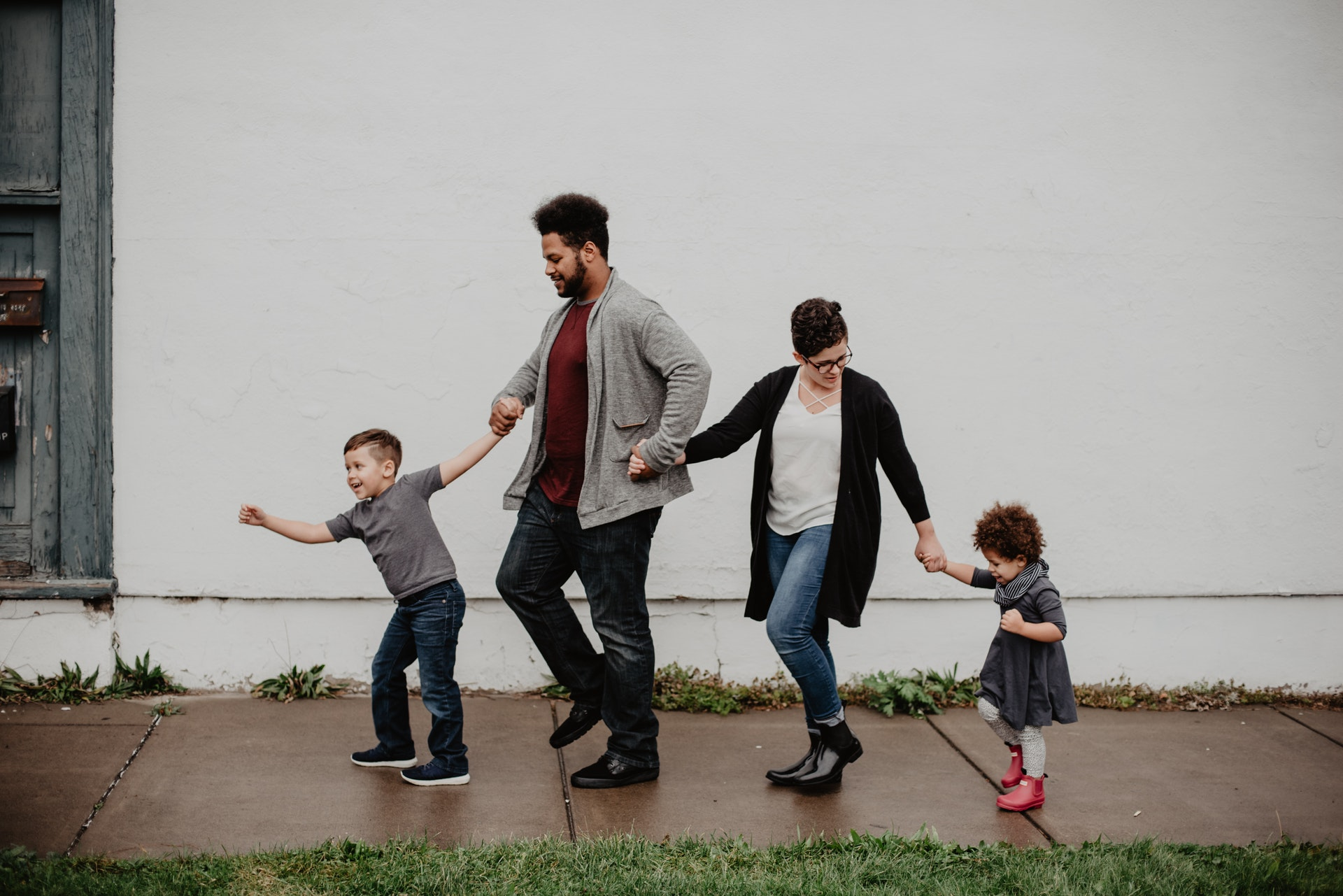 Family of four walking down the street holding hands and smiling