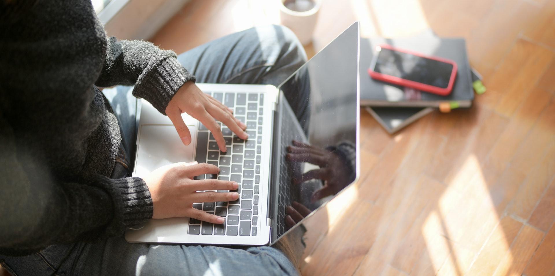 Female student sitting on floor studying real estate prelicensing online