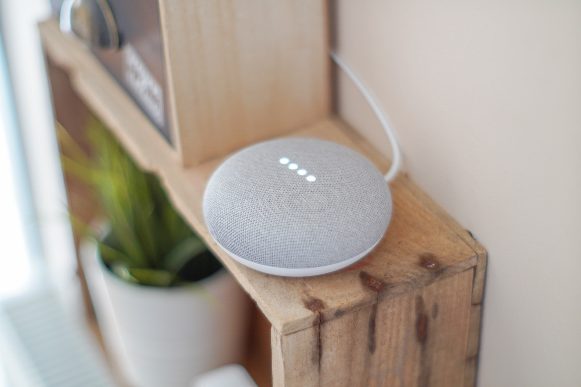 Grey google home mini on shelf
